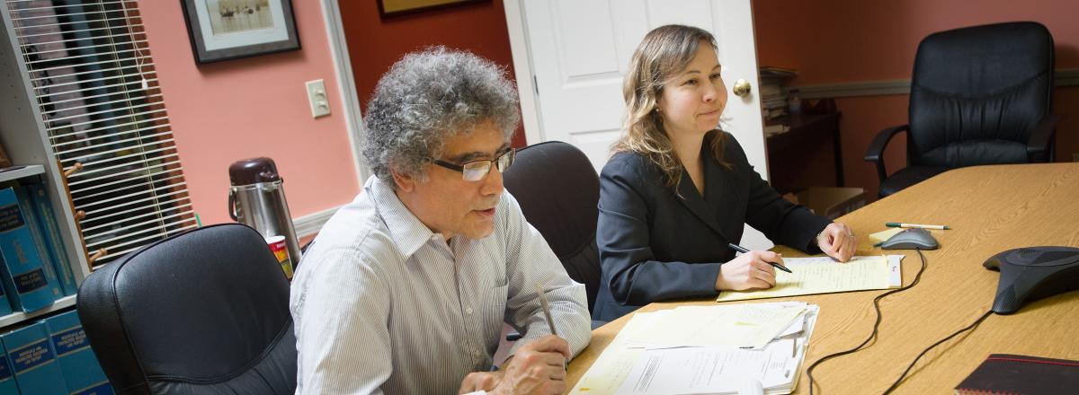 A picture of two PTLA attorneys, Frank and Katie, sitting at a conference table in a library, looking at legal papers